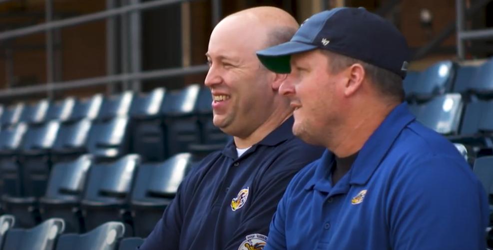 Image of two baseball team employees